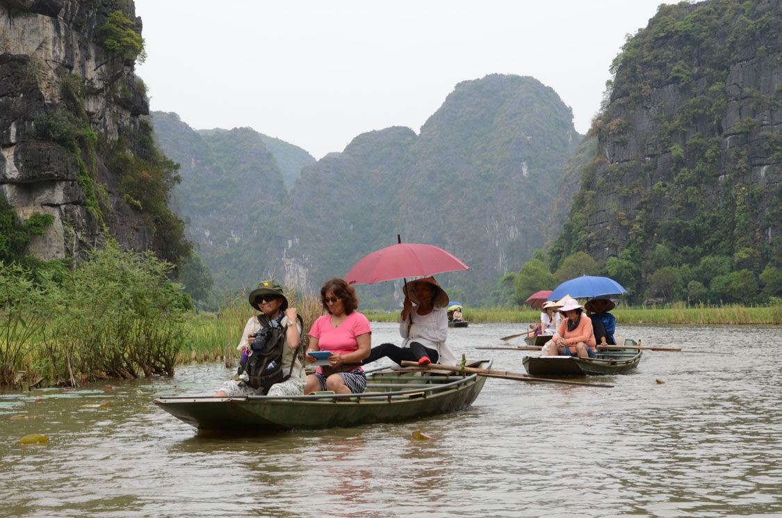 CRUISING DOWN THE NGO DONG RIVER TO THE TAM COC CAVES IN FLAT-BOTTOMED SAMPANS THAT ARE ROWED BY FOOT.